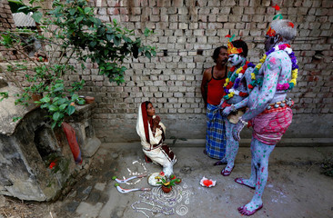 A woman seeks blessings from devotees with their bodies painted, before the start of a ritual as part of the annual Shiva Gajan religious festival at Sona Palasi village