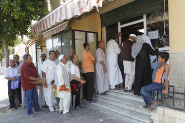 Civilians stand in line to buy bread in the city of Tripoli