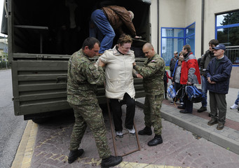 Soldiers help a woman out from an army truck, which has been transporting people from the flooded village of Devin, in Bratislava