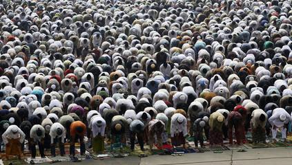 Muslims attend prayer along a street to celebrate the festival of Eid al-Adha in Jakarta