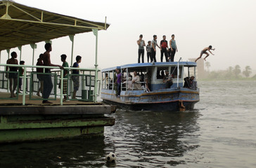 Children dive in the Nile from above a ferry used to transport people from one side of the Nile to the other, to escape the hot weather during a heat wave in Cairo