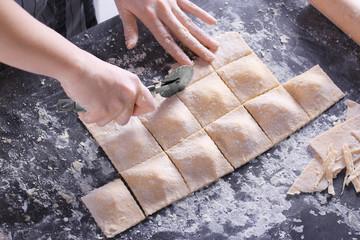 Woman making ravioli on table