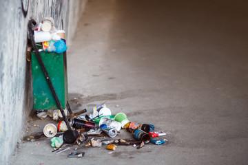 Trash receptacle on the street. Trash on the sidewalk