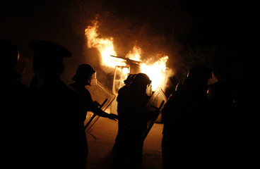 Bulgarian riot police walk in front of a burning guardhouse outside a house in the village of Katunitsa