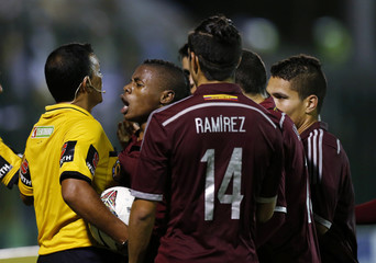 Bolivian referee Mancilla is surrounded by players of Venezuela before disallowing a goal by Uruguay during their Group B soccer match for the South American under-20 Championship in Maldonado