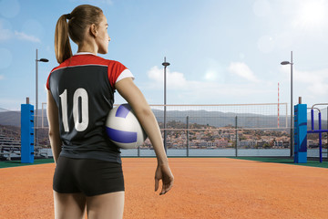 Female volleyball player standing with ball