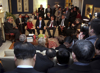 China's Vice President Xi Jinping talks with area residents in the home of Roger and Sarah Lande in Muscatine