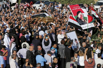 Relatives of former Iraqi foreign minister Tariq Aziz, and supporters of the Baath Party in Jordan walk with his casket during his funeral at the cemetery in Madaba city, near Amman