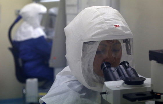 A doctor uses a microscope to look at virus samples in a Biosafety Level III laboratory in Lima
