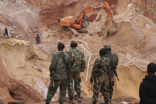 Suriname wildcat miners use an excavator to recover the bodies of seven miners who died when the 20-meter-high dirt wall of a gold mine collapsed, at Money Hill