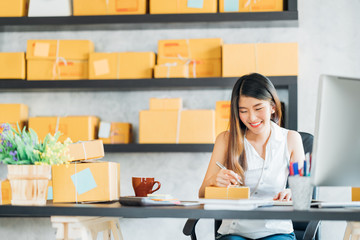 Young Asian small business owner working at home office, taking note on purchase orders. Online marketing packaging delivery, startup SME entrepreneur or freelance woman concept
