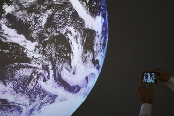 A participant takes a picture of a replica of the Earth during the World Climate Change Conference 2015 (COP21) at Le Bourget
