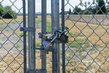Three locks secure gate on fence