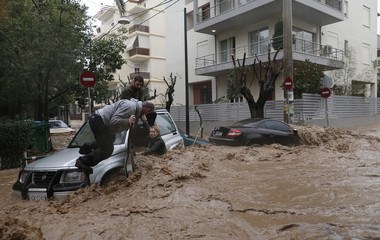 A woman stuck in her car is rescued from flood waters by residents during heavy rain in Chalandri suburb north of Athens