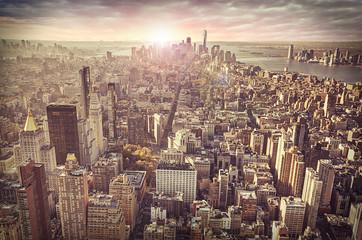 New York city skyline, sunrise in background.
