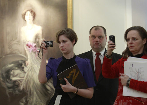 Visitors take pictures, with Giovanni Boldini's 'Portrait of Madame E. Doyen' in the background, during the Fine Art Auction House Christie's Moscow exhibition