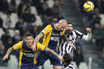 Juventus' Chiellini jumps for the ball with Hellas Verona's Rodriguez  and Greco during their Italian Serie A soccer match in Turin