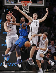 Dallas Mavericks O.J. Mayo reacts as he loses ball while being triple-teamed by Brooklyn Nets Brook Lopez, Mirza Teletovic and Deron Williams in NBA game in New York