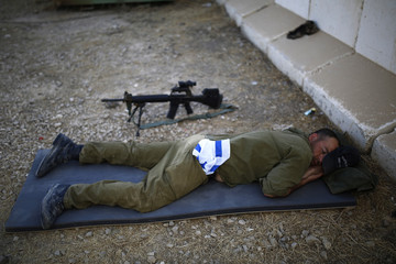 An Israeli soldier sleeps at a military post just outside the border with the Gaza Strip