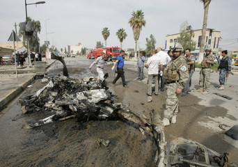 Security personnel inspect the remains of a vehicle used in a bomb attack in Kirkuk