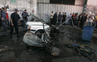 Members of Hamas' security forces stand around a car that exploded in Gaza