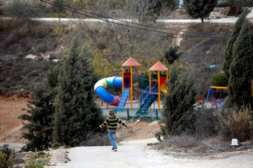 An Israeli boy walks near a playground in the Jewish settler outpost of Amona in the West Bank