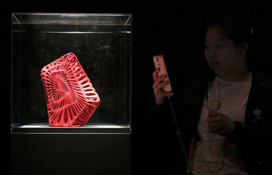 A woman takes a picture of the 3D printed shoes by Mexican architect Fernando Romero's during Milan Design Week