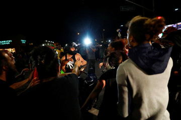 A motorcyclist is surrounded by protesters upon crashing his bike after he was pulled off of it by people protesting the death of Alfred Olango in El Cajon