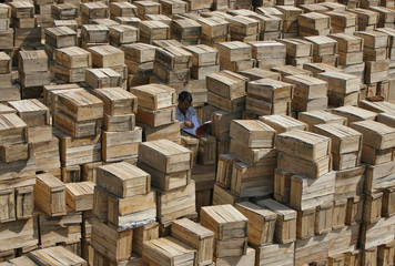 A trader checks an account book amid stacked wooden boxes of apples at a wholesale fruit market on the outskirts of Jammu