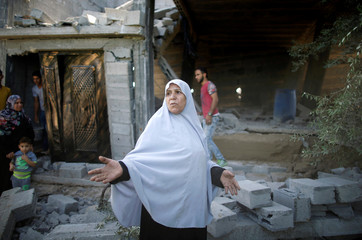 Palestinian woman gestures as she inspects the scene of what witnesses said was an Israeli air strike carried out on Wednesday, east of Gaza City