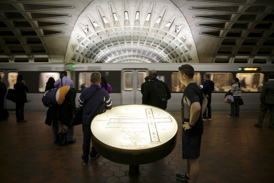 Commuters stand next to a station map as a train arrives at the Gallery Place-Chinatown station ahead of a shutdown in Washington