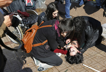 Protesters help a handicapped protester, who fell from her wheelchair after tear gas was shot towards them, during a demonstration in Ankara