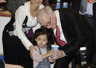 Billionaire financier and Berkshire Hathaway CEO Warren Buffett gives a cup of DQ ice cream to a Chinese girl during his visit to a new Dairy Queen store in Beijing