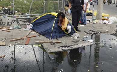 A woman leaves her tent next to Metropolitan Civil Guard after smoking crack in part of Sao Paulo's Luz neighborhood known to locals as Cracolandia