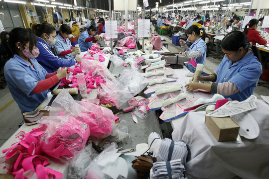 Employees work on an assembly line at a shoe factory in Tan Lap village