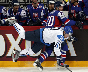 Finland's Hagman falls next to Slovakia's Dano during their 2013 IIHF Ice Hockey World Championship quarter-final match at the Hartwall Arena in Helsinki
