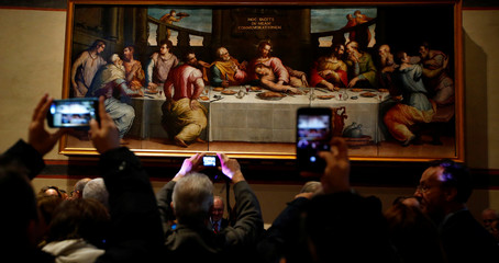 """Guests take pictures during the unveiling of Giorgio Vasari's """"Last Supper"""" painting after its restoration at the Opificio delle Pietre Dure in Florence"""