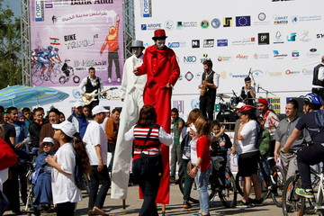 People look at clowns walking on stilts as they part in a march in support of cycling, clean transportation and to promote safe roads for cyclers and the handicapped in Tripoli