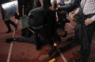 A riot policeman is injured during clashes with fans of Egypt's Al-Ahly after their African Super Cup soccer match against Tunisia's CS Sfaxien at Cairo Stadium