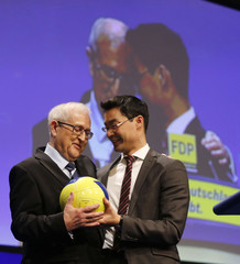 Faction leader of liberal Free Democratic Party Bruederle and party leader Roesler hold soccer ball during two-day party convention in Berlin