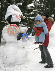 "A woman and her baby look at a ""Snowman with a baby"" exhibit in Krasnoyarsk"