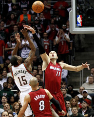 Miami Heat's Ilgauskas from Lithuania blocks the shot attempt from the Milwaukee Bucks' Salmons in the first half during their NBA basketball game in Milwaukee