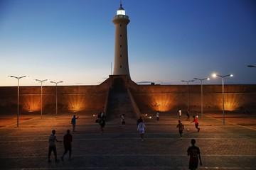 Boys play football in front of a lighthouse near Rabat's Medina