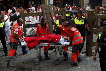 An injured runner is taken away by medical staff as carpenters remove the bull run barrier after the last running of the bulls of the San Fermin festival in Pamplona