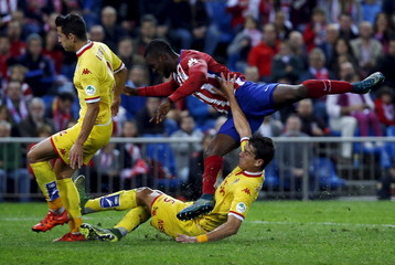 Atletico Madrid's Jackson goes airborne as he fights for the ball with Sporting Gijon's Hernandez and Espinosa during their Spanish first division soccer match at Vicente Calderon stadium in Madrid