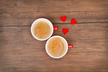 Cups of coffee with hearts on wooden table