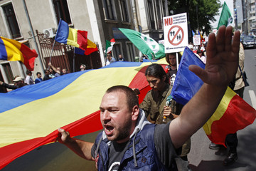 A member of the far-right Noua Dreapta (New Right) group gestures while holding a huge Romanian national flag during a march against the Gay Fest 2013 parade in Bucharest