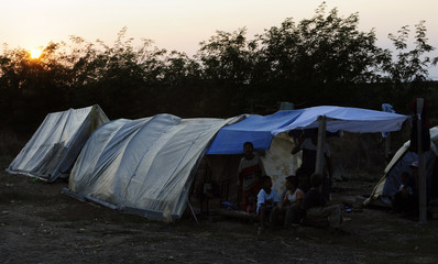 Members of the Roma community are seen in the tent area in which they live, at the Read Hills vineyards near Negotino
