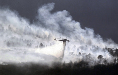 A helicopter drops water on the Waldo Canyon fire burning behind the U.S. Air Force Academy, west of Colorado Springs