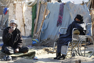 People sit outside shelter at Umm al-Banin IDP camp in Baghdad